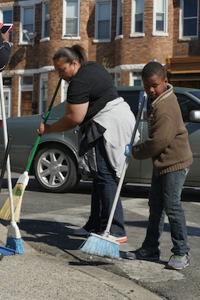 West Baltimore residents sweep broken glass and debris outside a store damaged by rioters earlier this week. (CNS photo/Karen Osborne, Catholic Review)