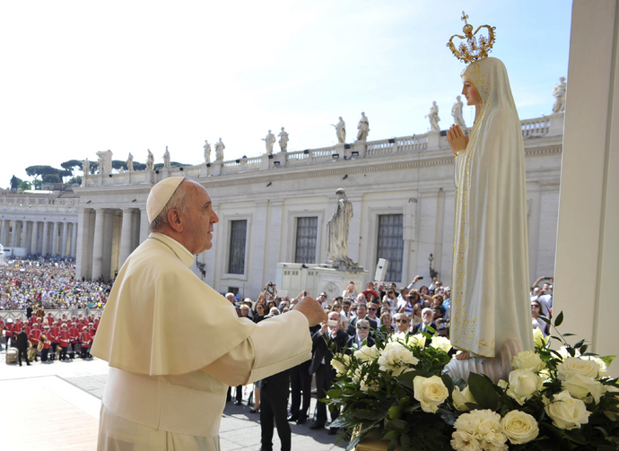 Pope Francis prays in front of a statue of Our Lady of Fatima during his general audience in St. Peter's Square at the Vatican May 13. The statue, which was present for the May 13 feast of Our Lady of Fatima, is a copy of the original in Fatima, Portugal. (CNS photo/L'Osservatore Romano, pool)