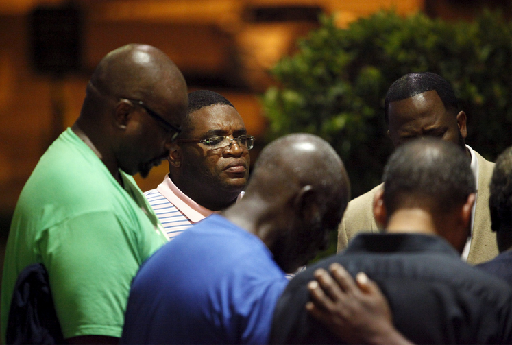 Small prayer circle forms nearby where police respond to shooting at historic black church in Charleston, S.C.