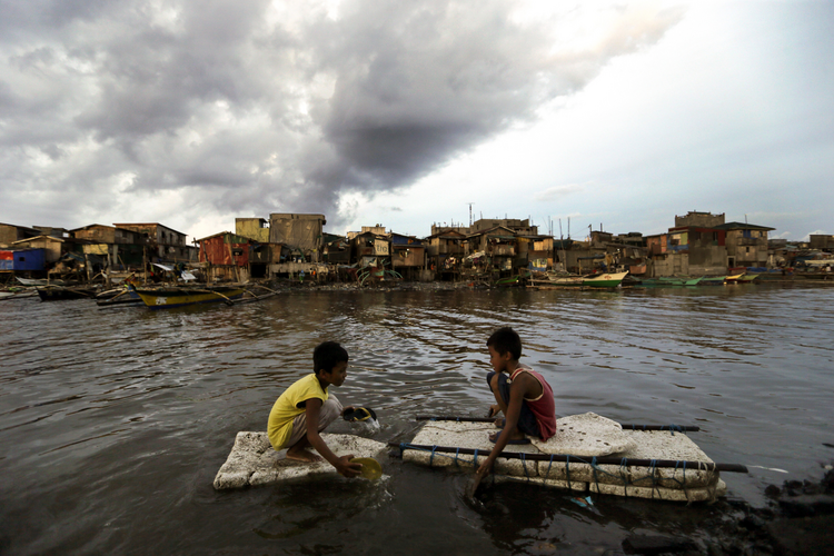 Children paddle in water in Navotas City, Philippines. (CNS photo/Ritchie B. Tongo, EPA)