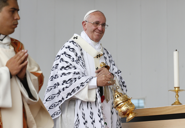 Pope Francis smiles at someone while using incense during Mass in Bicentennial Park in Quito, Ecuador, July 7. (CNS photo/Paul Haring)