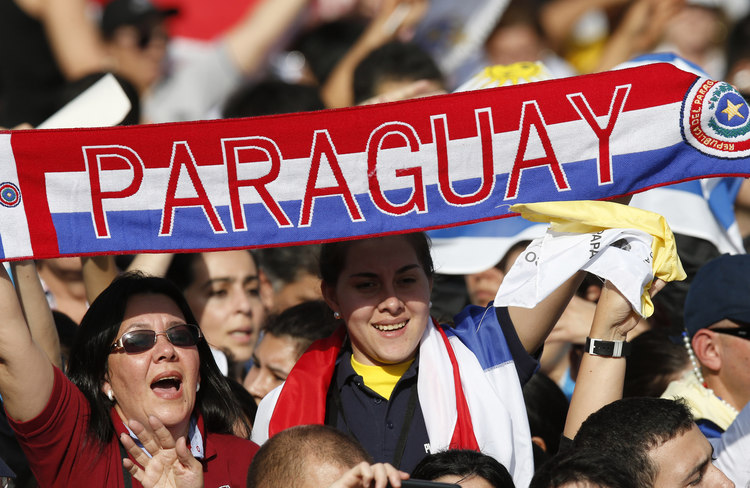 Woman holds a banner with Paraguay's national colors before Pope Francis' arrival to celebrate Mass in Nu Guazu Park in Asuncion, Paraguay, July 12. (CNS photo/Paul Haring)