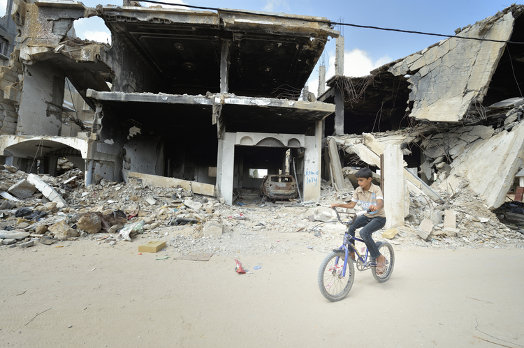 RIDE AMONG THE RUINS: A boy rides his bike amid the ruins of Khan Younis, Gaza Strip, June 9. Houses in the area were destroyed during the 2014 war between Israel and the Hamas government of Gaza. (CNS photo/Paul Jeffrey)