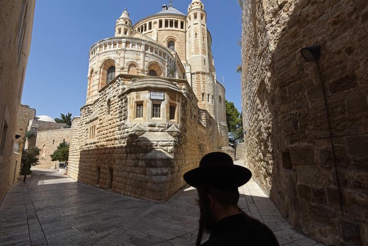 An Ultra-Orthodox Jew walks past the Dormition Abbey on Mt. Zion in Jerusalem in July. (CNS photo/Debbie Hill)