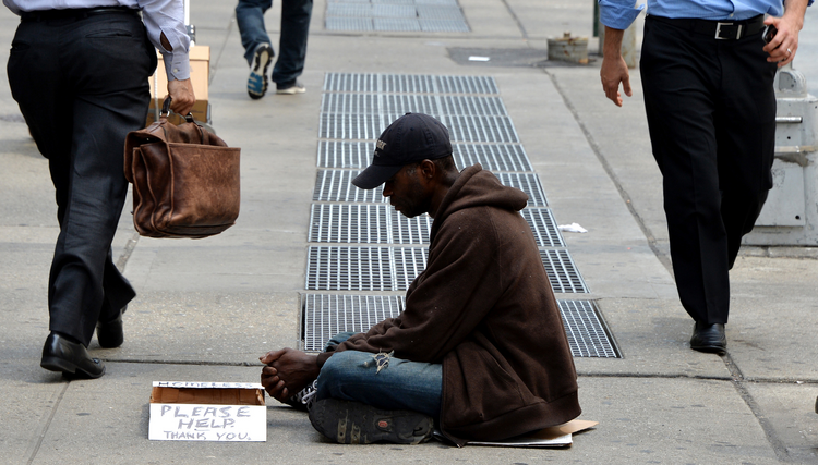 In this June 16, 2014, file photo, a homeless man sits on a sidewalk in New York City. (CNS photo/Justin Lane, EPA)