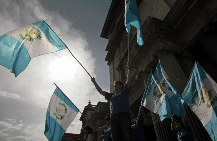 Guatemalan demonstrators wave national flags as they ask Guatemalan President Otto Perez Molina to resign during a protest in front of the National Palace of Culture in Guatemala City Aug. 22. (CNS photo/Esteban Biba, EPA)