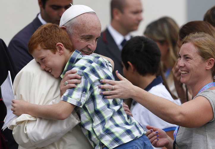 Pope Francis embraces Simone Zanini, 8, while greeting the disabled during his general audience in St. Peter's Square at the Vatican Sept. 2. (CNS photo/Paul Haring)