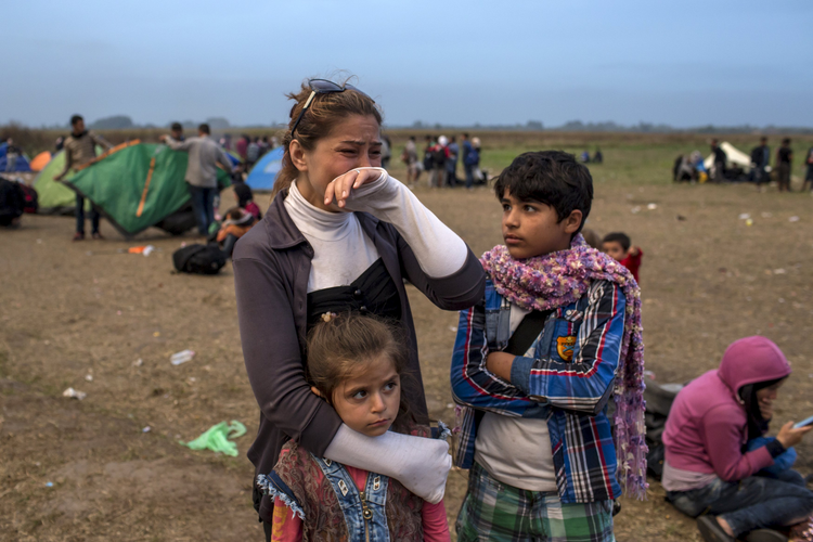 A migrant from Syria cries as she stands with her children on a field after crossing into Hungary from the border with Serbia near the village of Roszke Sept. 5. (CNS photo/Marko Djurica, Reuters)