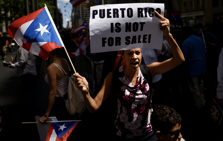 Woman protests near the office of a hedge fund manager in New York Aug. 13 over the financial crisis gripping Puerto Rico. A Senate committee held hearings Oct. 22 to discuss solutions to the crisis. (CNS photo/Justin Lane, EPA)