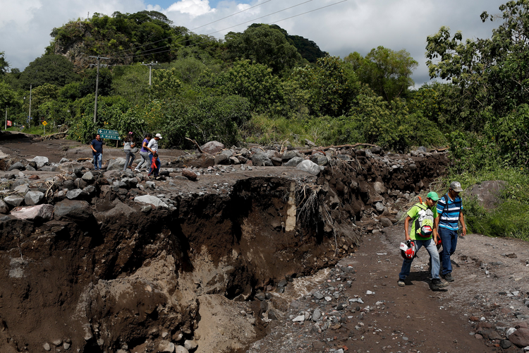 Residents walk near a damaged bridge in Comala, Mexico, Oct. 24. (CNS photo/Tomas Bravo, Reuters)