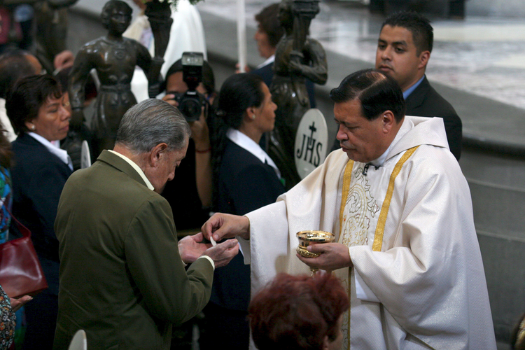 Cardinal Norberto Rivera Carrera of Mexico City distributes Communion during Mass in early May at Mexico City's Metropolitan Cathedral. (CNS photo/Ricardo Castelan, EPA)