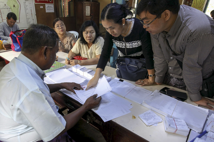 A staff member of a polling station assists people to check their names on final voter list during early voting in Mandalay, Myanmar, Nov. 1. Myanmar will hold its nationwide general elections Nov. 8. (CNS photo/Hein Htet, EPA)