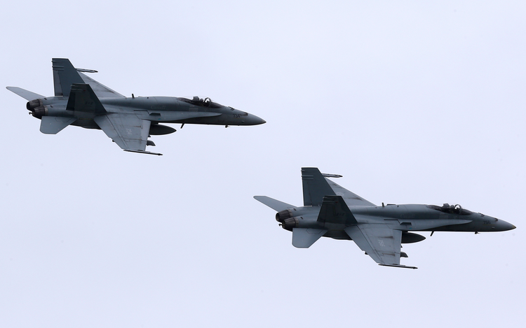 In this May 31, 2014, file photo, two Royal Canadian Air Force F-18 Hornet jets fly over Romania. Canada's new government has decided to stop airstrikes against Islamic State in the Middle East. (CNS photo/Mircea Rosca, EPA)