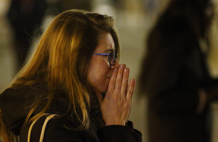 A woman mourns in Republique square in Paris Nov. 14 as people gather in memory of victims of terrorist attacks. Coordinated attacks the previous evening claimed the lives of 129 people. The Islamic State claimed responsibility. (CNS photo/Paul Haring)