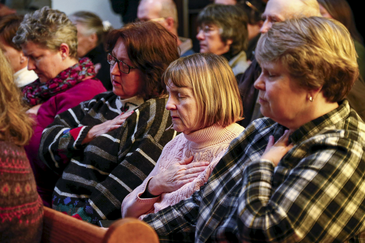 People pray during a vigil at All Souls Unitarian Universalist Church Nov. 28, the day after a gunman opened fire on a Planned Parenthood clinic in Colorado Springs, Colo. (CNS photo/Isaiah J. Downing, Reuters)