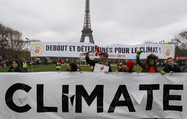 "Environmentalists hold a banner that reads, ""Standing and Determined for the Climate,"" during a Dec. 12 protest near the Eiffel Tower in Paris as the U.N. climate conference ended. (CNS photo/Mal Langsdon, Reuters)"