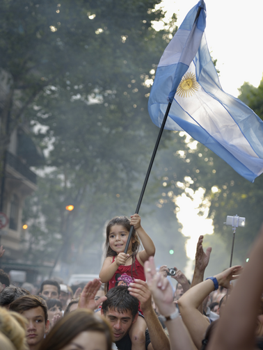 A girl carries an Argentine flag during a rally on President Cristina Fernandez de Kirchner's last day in office Dec. 10. (CNS photo/Paul Jeffrey)