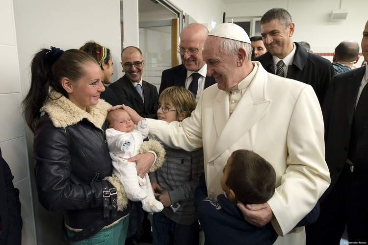Pope Francis blesses a baby during a visit to a Caritas center for the homeless near the Termini rail station in Rome Dec. 18. The pope opened a Door of Mercy at the center. (CNS photo/L'Osservatore Romano, handout)