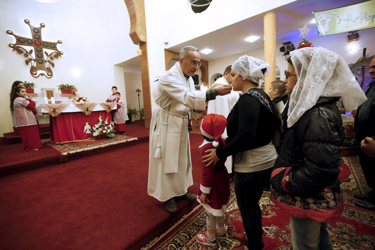 A priest gives Communion during Christmas Eve Mass at Sacred Heart Catholic Church in Baghdad. (CNS photo/ Thaier Al-Sudani, Reuters)