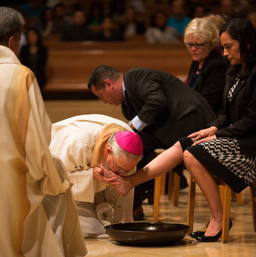 Los Angeles Archbishop Jose H. Gomez kisses the foot of a woman during Holy Thursday Mass in 2014 at the Cathedral of Our Lady of the Angels in Los Angeles. Following a request by Pope Francis, the Vatican issued a decree Jan. 21 specifying that the Holy