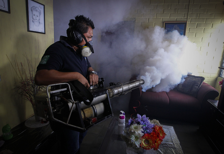 A worker of the Salvadoran Ministry of Health fumigates a house Jan. 21 near San Salvador. Salvadoran authorities began the fumigation process to reduce the presence of the mosquito that transmits the Zika virus. (CNS photo/Oscar Rivera, EPA)