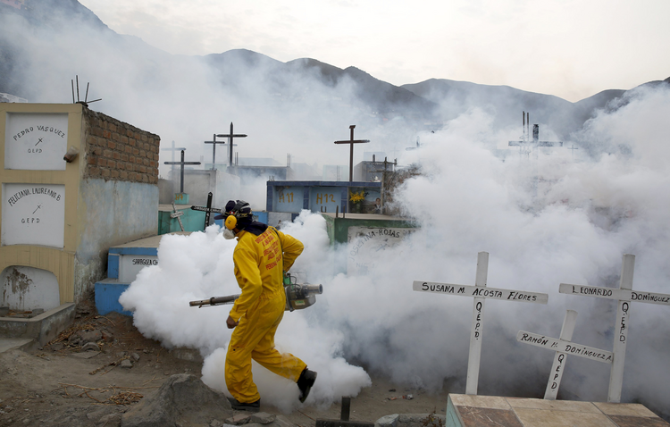 A health worker carries out fumigation as part of preventive measures against the Zika virus and other mosquito-born diseases at a cemetery on the outskirts of Lima, Peru. (CNS photo/Mariana Bazo, Reuters)
