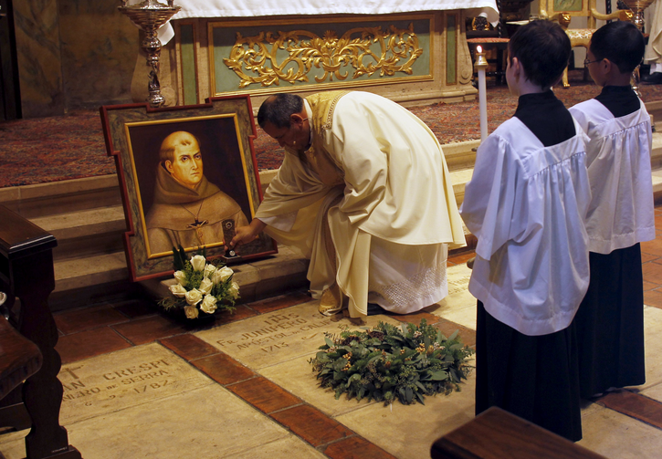 Father Miguel Rodriguez sets a relic on the tomb of St. Junipero Serra during Mass at the Carmel Mission Basilica in Carmel, Calif., Sept. 23, 2016, the day the Spanish missionary and founder of the California mission system was cannonized by Pope Francis in Washington. (CNS photo/Michael Fiala, Reuters)