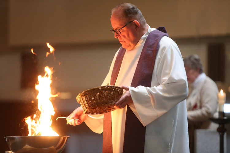 Father Thomas Kommers of St. Joseph Church in Red Wing, Minn., puts palms in a bowl and burns them during an Ash Wednesday prayer service Feb. 10. (CNS photo/Dave Hrbacek, The Catholic Spirit)
