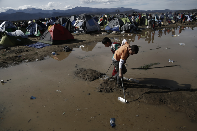Migrant children play in water at a refugee camp in Idomeni, Greece, March 8. (CNS photo/Yannis Kolesidis, EPA)