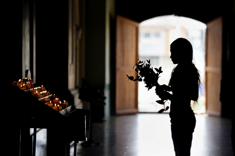 A woman prays in Cali, Colombia, in this April 13, 2014, file photo. (CNS photo/Christian Escobar Mora, EPA)