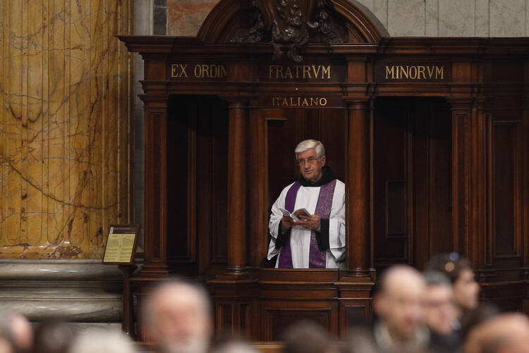A priest participates from his confessional as Pope Francis leads a Lenten penance service in St. Peter's Basilica at the Vatican in this March 13, 2015, file photo. (CNS photo/Paul Haring)