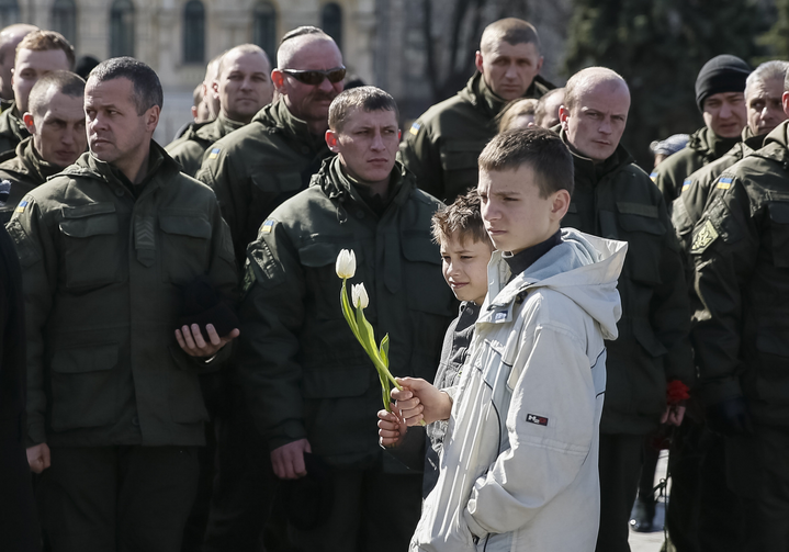 Ukrainian boys in Kiev hold flowers March 16 during a ceremony marking the second anniversary of people killed in the pro-Russian separatist conflict. (CNS photo/Gleb Garanich, Reuters)
