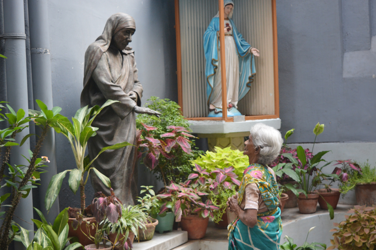 Margaret Rose of Kolkata, India, prays before a statue of Blessed Teresa at the headquarters of the Missionaries of Charity March 18. (CNS photo/Saadia Azim)