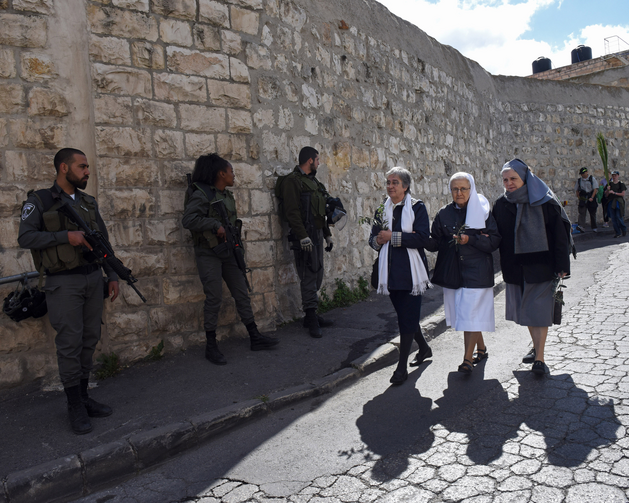 Women religious carry olive branches past Israeli border police before the annual Palm Sunday procession on the Mount of Olives overlooking the Old City of Jerusalem on March 20. (CNS photo/Debbie Hill)