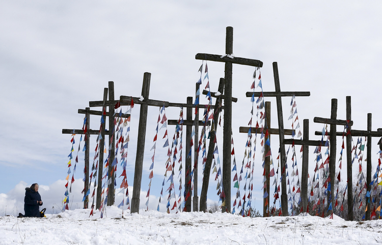 A woman prays on a hill with wooden crosses after a procession celebrating Palm Sunday in Oshmiany, Belarus, March 20. (CNS photo/Vasily Fedosenko, Reuters)
