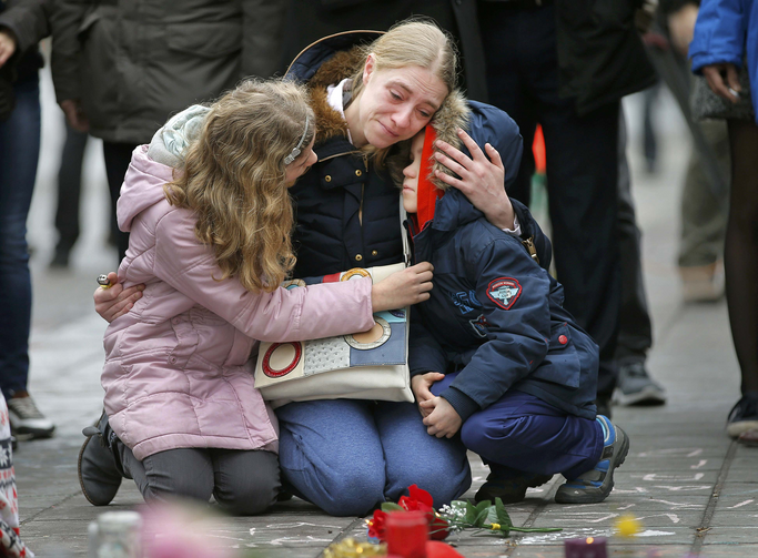 A woman consoles her children at a street memorial March 23 following bomb attacks in Brussels. Three nearly simultaneous attacks March 22 claimed the lives of dozens and injured more than 200. (CNS photo/Vincent Kessler, Reuters)