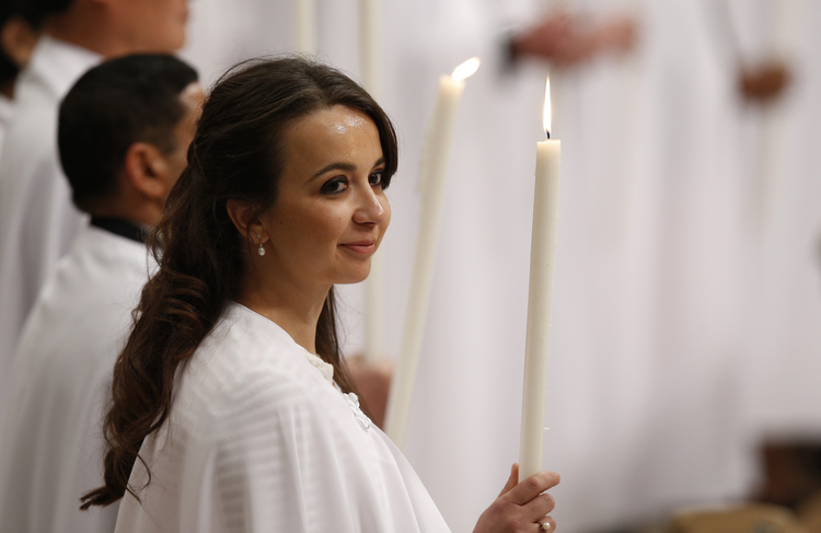 A new member of the church holds a candle as Pope Francis celebrates the Easter Vigil in St. Peter's Basilica at the Vatican March 26. The pope baptized 12 people at the vigil. (CNS photo/Paul Haring)