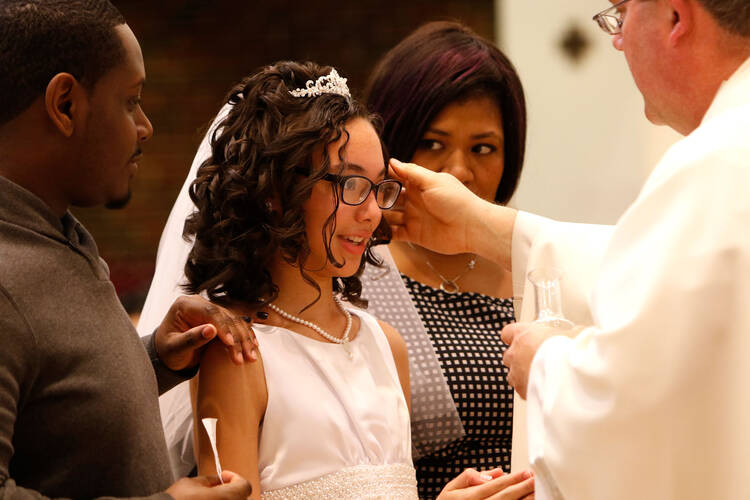 Dejia Solomon, 12, is anointed with chrism by Father Christopher Nowak during Mass April 2 at St. John of God Church in Central Islip, N.Y.