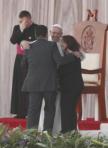 Pope Francis embraces Humberto and Claudia Gomez, who are married civilly but not in the church, during a meeting with families at the Victor Manuel Reyna Stadium in Tuxtla Gutierrez, Mexico, Feb. 15.