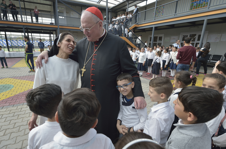 Cardinal Timothy M. Dolan of New York embraces Dominican Sister Muntahah Haday at the Al Bishara School run by the Dominican Sisters of St. Catherine of Siena in Ankawa, Iraq, April 9. (CNS photo/Paul Jeffrey)