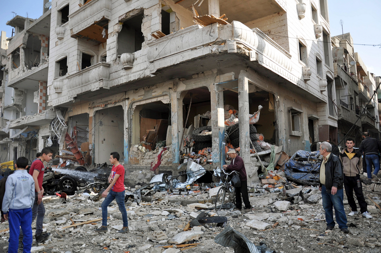 People walk in front of destroyed buildings in late February at the site of a twin bomb attack in the city of Homs, Syria. (CNS photo/EPA)