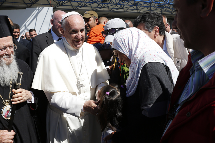 Pope Francis greets refugees who are traveling to Rome with him at the international airport in Mytilene on the island of Lesbos, Greece, April 16, 2016. The pope brought 12 refugees to Italy on his plane. (CNS photo/Paul Haring)