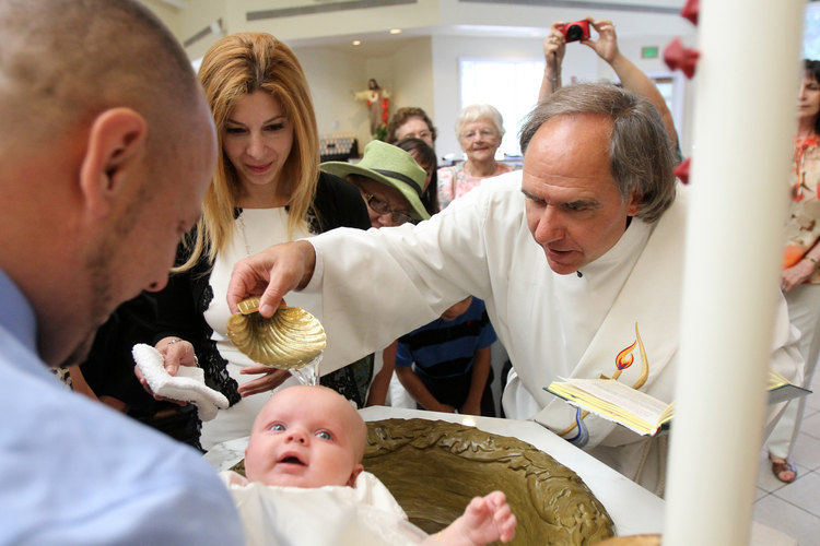 Deacon Mark Herrmann baptizes 4-month-old Victoria Marie Domke at St. Jude Church in Mastic Beach, N.Y., in 2013. (CNS photo/Gregory A. Shemitz)