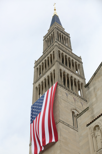 A large American flag is seen hanging from the bell tower of the Basilica of the National Shrine of the Immaculate Conception in Washington July 4, 2015. The U.S. bishops' fifth annual Fortnight for Freedom opens June 21. (CNS photo/Bob Roller)