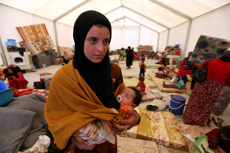 A displaced woman carries her sleeping child June 15 at a refugee camp near Mosul, Iraq. (CNS photo/Azad Lashkari, Reuters)