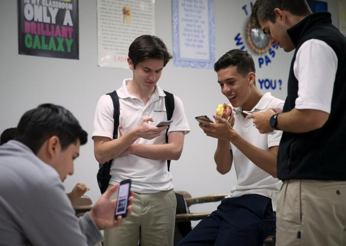 Students at St. Joseph Academy in Brownsville, Texas, check their smartphones during lunch May 3. (CNS photo/Tyler Orsburn)