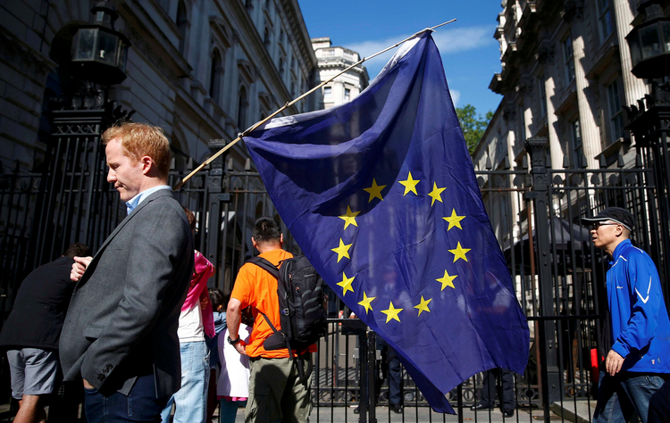 A man carries a European Union flag in London June 24, a day after voters in the United Kingdom decided to leave the EU. (CNS photo/Neil Hall, Reuters)