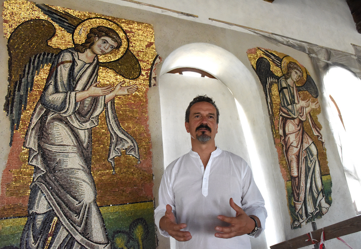 Giammarco Piacenti, CEO of the Piacenti restoration center, stands in front of angel mosaics in the Church of the Nativity July 5 in Bethlehem, West Bank. Restoration specialists from the center completed their work in June. (CNS photo/CNS/Debbie Hill)