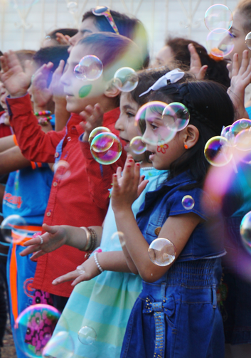 Syrian refugee children sing among floating bubbles during a graduation ceremony at the Latin Patriarchate School in Naour, Jordan, on July 11. (CNS photo/Dale Gavlak)