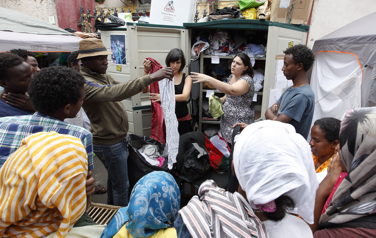 Refugees receive clothing from volunteers on a street in Rome on July 14. Several refugees said they were planning to head north to countries such as France and Germany. (CNS photo/Paul Haring)